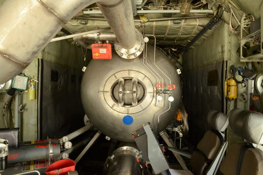 The front of the Modular Airborne Firefighting System inside a Nevada Air National Guard C-130, just before it is deployed to help fight the Northern California fires. Two people control the system from the seats inside the cargo bay.