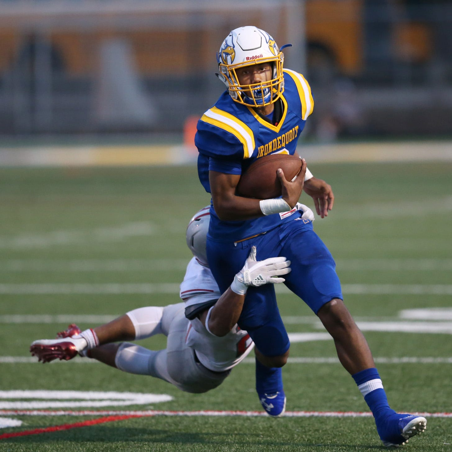 Irondequoit quarterback Freddy June Jr. is tackled from behind by Canandaigua's AJ Clifford as he scrambles downfield for yardage during their game Saturday, Sept. 16, 2017.