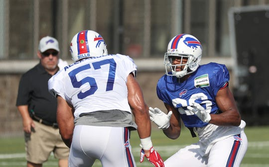 Bills running back Taiwan Jones blocks linebacker Lorenzo Alexander during training camp.