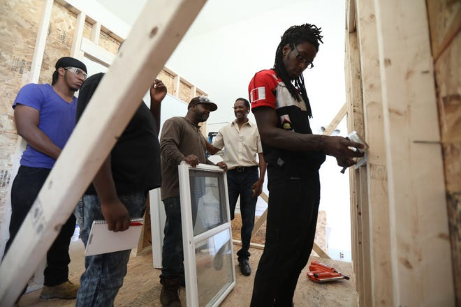 Lenzy Blake II, 28, of Rochester measures an area where the students will install a window.