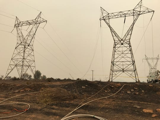 Downed power lines near Keswick Dam Road dot the patrol route of Redding Police officer Josh Tracy, who scouts neighborhoods evacuated in the Carr Fire for looters and any other issues.