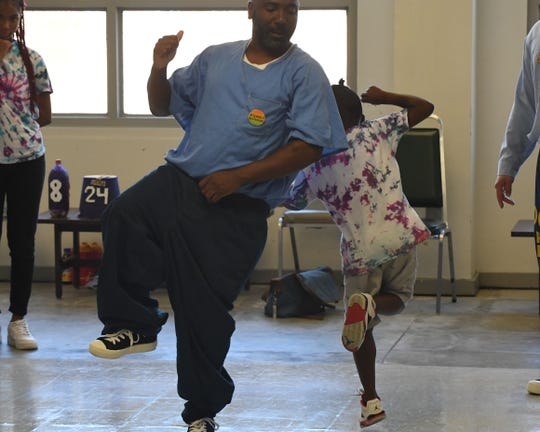 Evan Freeman Sr. and Evan Freeman Jr. dance during Camp Grace at Salinas Valley State Prison Friday.