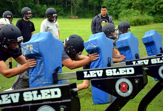 Buffalo Gap football players hit the blocking sled during their first day of practice on Monday, July 30, 2018, at Buffalo Gap High School in Swoope, Va.