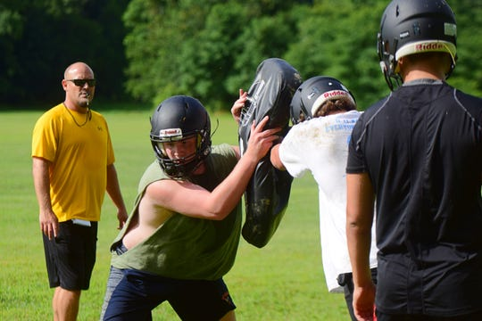 Buffalo Gap head football coach Andy Cline, left, watches his players go through a drill during their first day of practice on Monday, July 30, 2018, at Buffalo Gap High School in Swoope, Va.