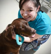Sandy Watters smiles while spending time with Praline Tuesday, July 31, at the Tri-County Humane Society.