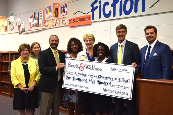 Members from Leon County Schools, Second Harvest of the Big Bend and Scott & Wallace stand with a check for $1,500 for Conley Elementary School to stock its food pantry