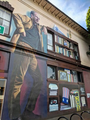"""Ken Kesey, the author of """"One Flew Over the Cuckoo's Nest,"""" is honored on a two-story building in his hometown of Springfield, Oregon. The city, adjacent to Medford, is also the fictional home of the Simpsons TV series. A walking tour of the town reveals Homer Simpson is equally regarded as a hometown hero. He's earned his own mural."""