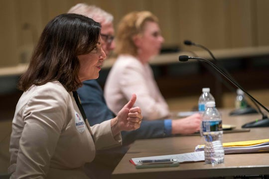 Kathy K. McGuiness, front, a candidate for State Auditor, answers questions during a debate in Dover while Dennis E. Williams and Kathleen Davies, back, listen.