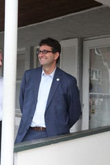 New Castle County Executive Matt Meyer stands on the front porch in July of an Overlook Colony residence in Claymont that county government hoped to bring to sheriff sale.