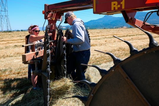 In this Wednesday, July 11, 2018 photo, Marie Bowers, center, troubleshoots a raker machine on her family's property in Coburg, Ore. Marie Bowers never thought she would spend her life working on a farm. But the 32-year-old woman who graduated from college and started a career in the financial industry has returned to her roots as a family farmer.