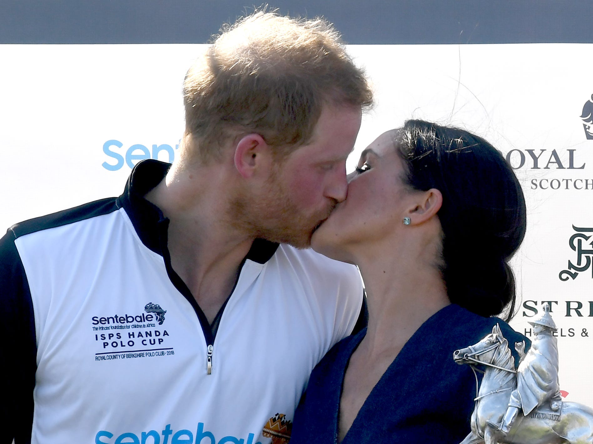 A kiss on the lips, even! Prince Harry and Duchess Meghan of Sussex smooch as they pose with the trophy after Harry's polo match at the Royal County of Berkshire Polo Club on July 26, 2018 in Windsor.