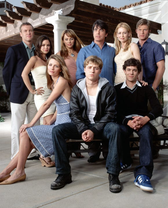 Style stars of the aughts. Top row, left to right: Tate Donovan, Rachel Bilson, Melinda Clarke, Peter Gallagher, Kelly Rowan and Chris Carmack. Seated, left to right: Mischa Barton, Benjamin McKenzie and Adam Brody.