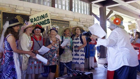 """Demonstrators, including the Raging Grannies singing group, gather at Smolenski Park in Mount Pleasant, Wis., on June 28, 2018 to protest the groundbreaking for the Foxconn manufacturing plant, which will receive more than $4 billion in state and local taxpayer subsidies. At far right in the line is activist Sheila Plotkin, whose group, We the Irrelevant, has documented instances in which the Legislature has approved bills over strong public opposition. """"Most people believe government no longer represents the people,"""" Plotkin said. """"It represents campaign donors, special interests, the wealthy."""""""