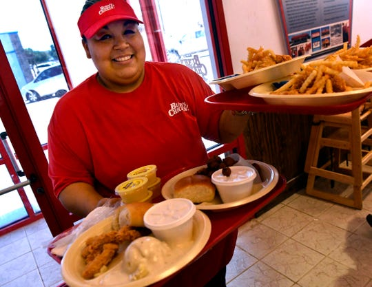 Esther Mata brings an order into the dining room at Bush's Chicken on E.N. 10th Street Wednesday. The newly-opened restaurant is in the location of the former Arby's and is next door to a Chicken Express.