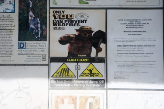 A small warning sign is part of a collage of information posted at the trailhead of Whitewater Falls in the Nantahala National Forest.