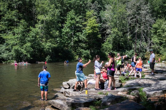 Visitors to DuPont State Recreational Forest sit on the bank of the Little River at the base of Hooker Falls Thursday, July 26, 2018.