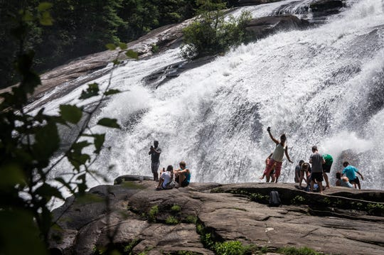 Visitors to DuPont State Recreational Forest sit on boulders in front of High Falls Thursday, July 26, 2018.