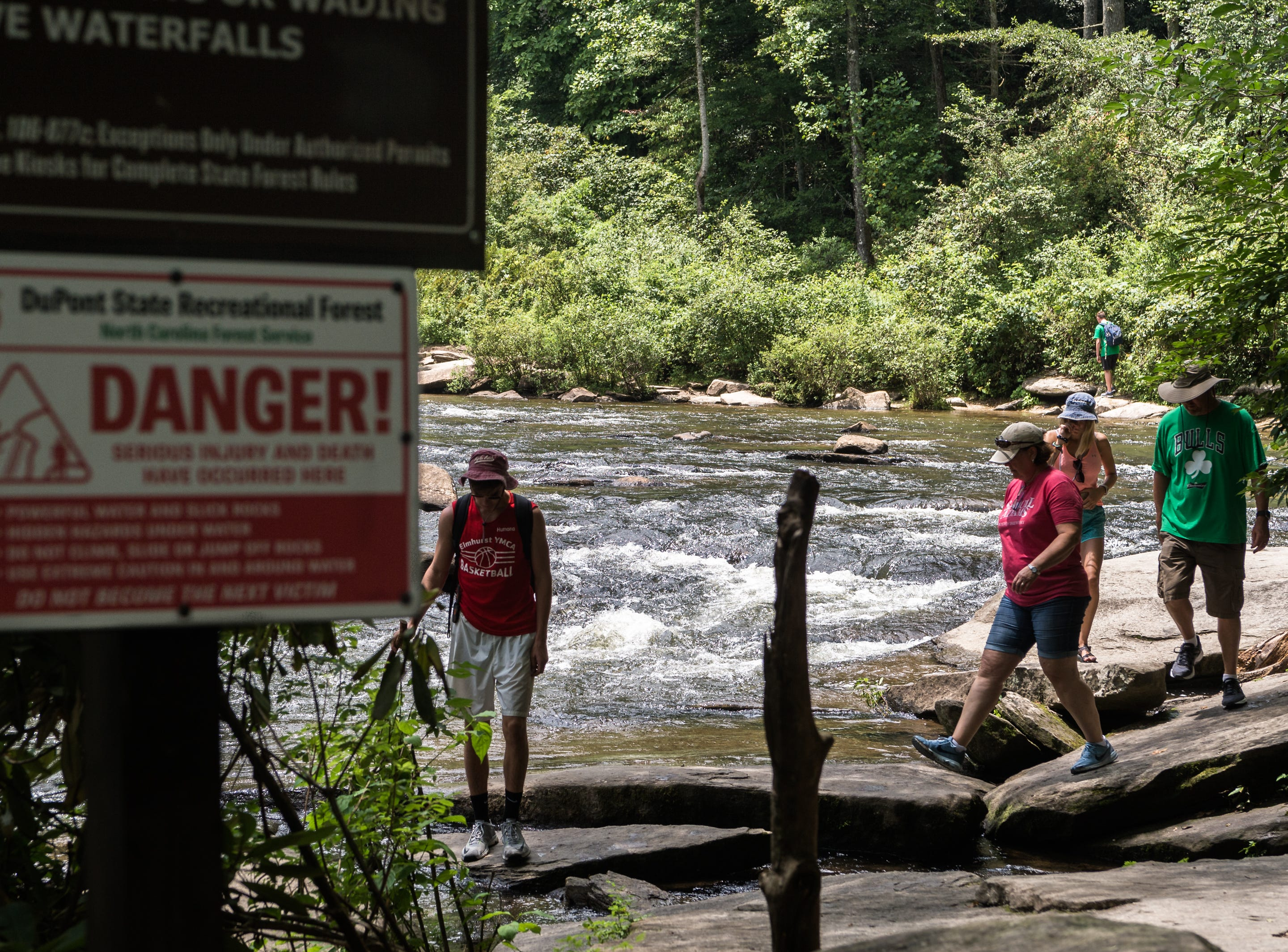 Visitors to DuPont State Recreational Forest hike back from High Falls Thursday, July 26, 2018.