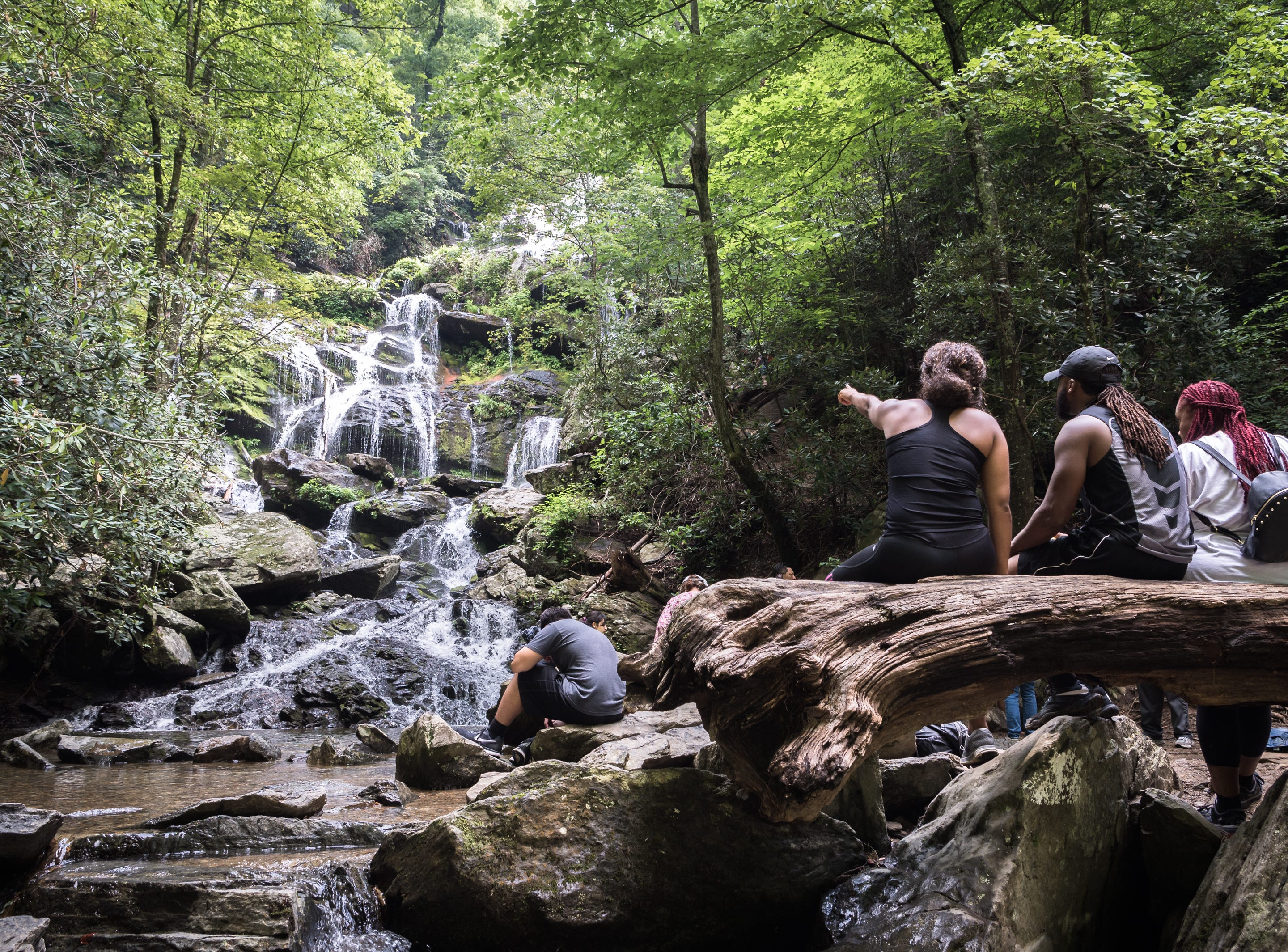 Visitors to Catabwa Falls in the Pisgah National Forest in Old Fort sit by the base of the falls Friday, July 13, 2018.