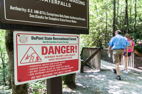 Visitors to DuPont State Recreational Forest walk down to the Triple Falls viewing area Thursday, July 26, 2018.