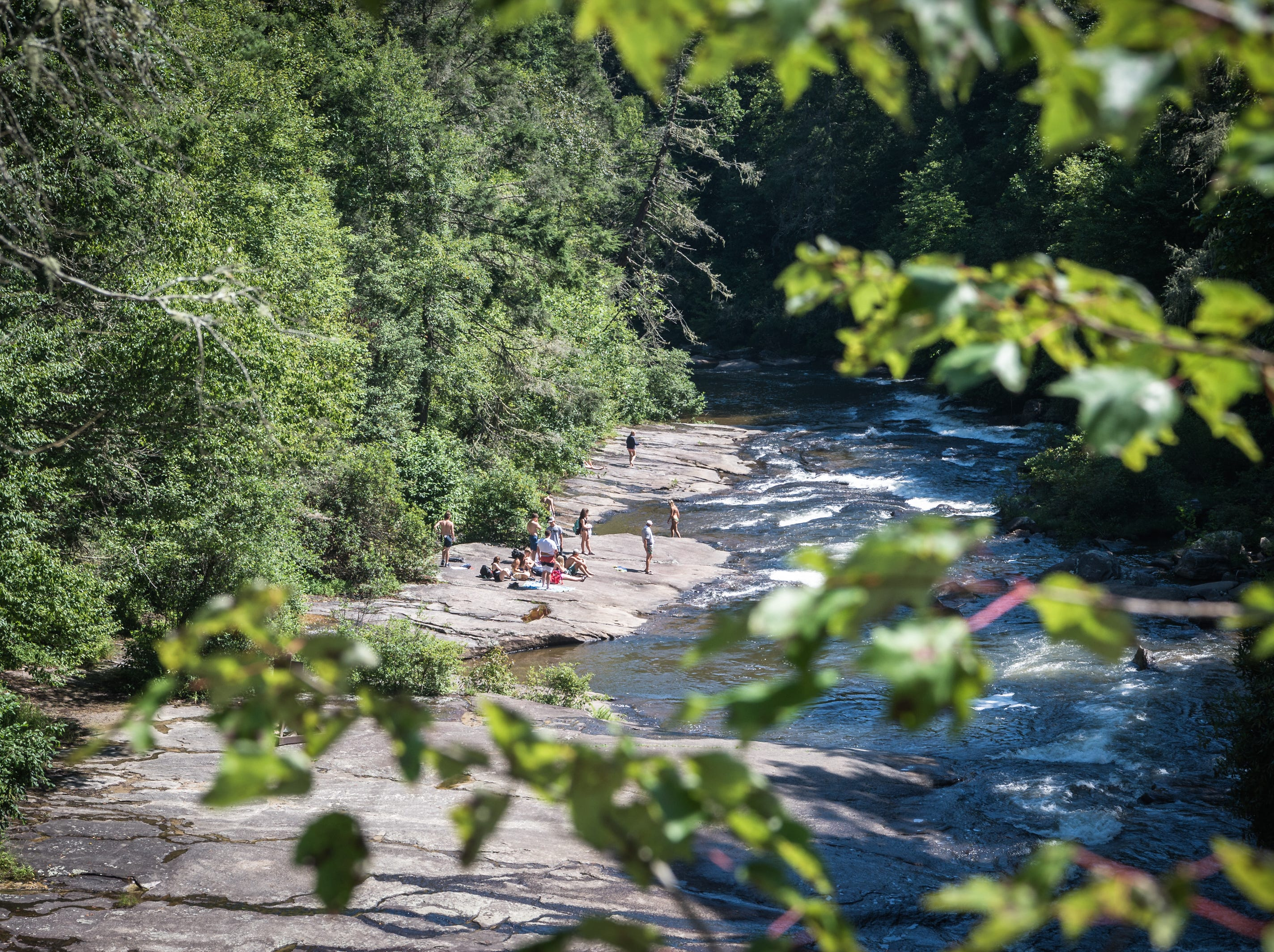 A group of visitors to DuPont State Recreational Forest sunbathe and swim downriver from Triple Falls Thursday, July 26, 2018.