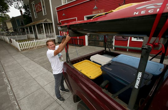 John Kuntz, owner of Olympic Outdoor Center, checks one of his kayaks atop his truck one last time before heading out from Port Gamble to the Columbia River on Wednesday. While he is paddling the Columbia River, Kuntz will have students following his adventure and using it as a basis of their elementary curriculum.