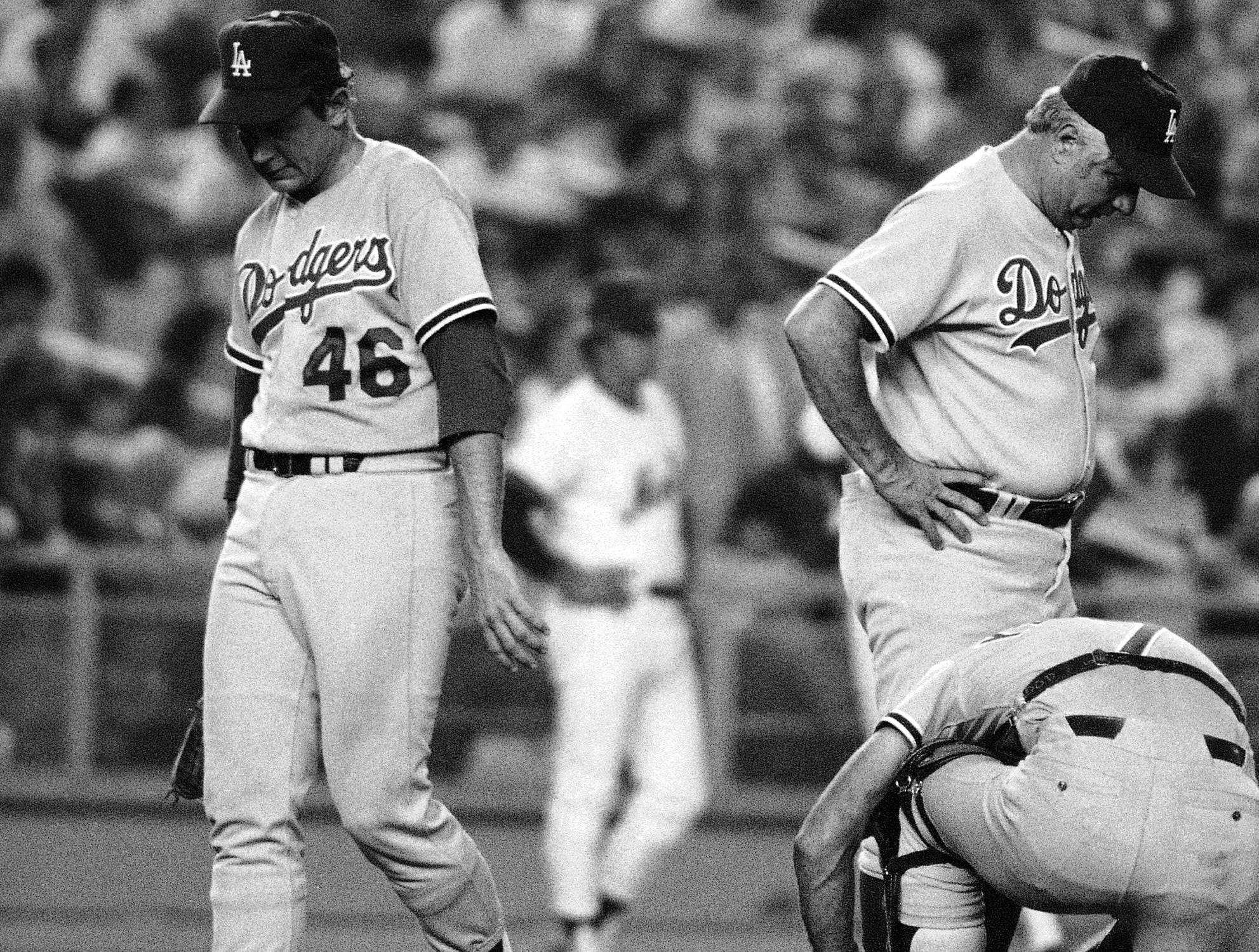 Los Angeles Dodgers pitcher Burt Hooton, left, joined by his manager Tom Lasorda eye the ground at the Shea Stadium in New York, July 12, 1979 mound as catcher Steve Yeager ties his shoes laces after Lasorda made the first inning trip to remove his pitcher from the game. The New York Mets had record heights in the inning, seven unearned credited to Hooten. The Dodgers, who were National League champions in 1978 are in last place in the National League west, entering the game 16 ½ games out of first. (AP Photo/Stubblebine)