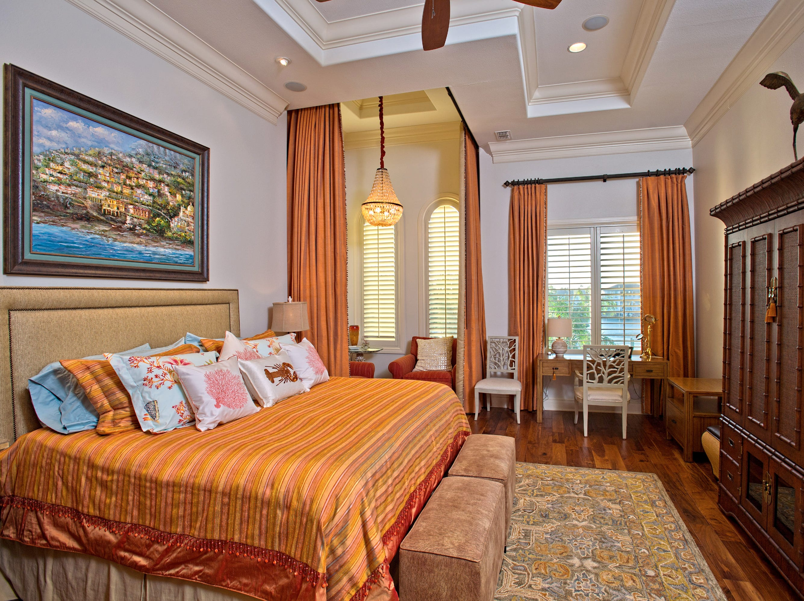 The spacious master bedroom has a majestic recessed ceiling with wonderful crown molding, a sitting area, Brazilian hardwood flooring and water views.