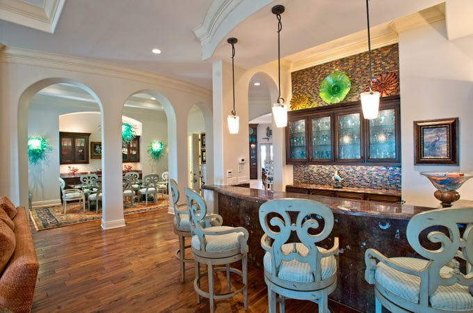 This amazing bar area anchors the living space .  The space features a bar with African fossil inlaid limestone, a mosaic tile wall with glass cabinets and seating for 4 plus.