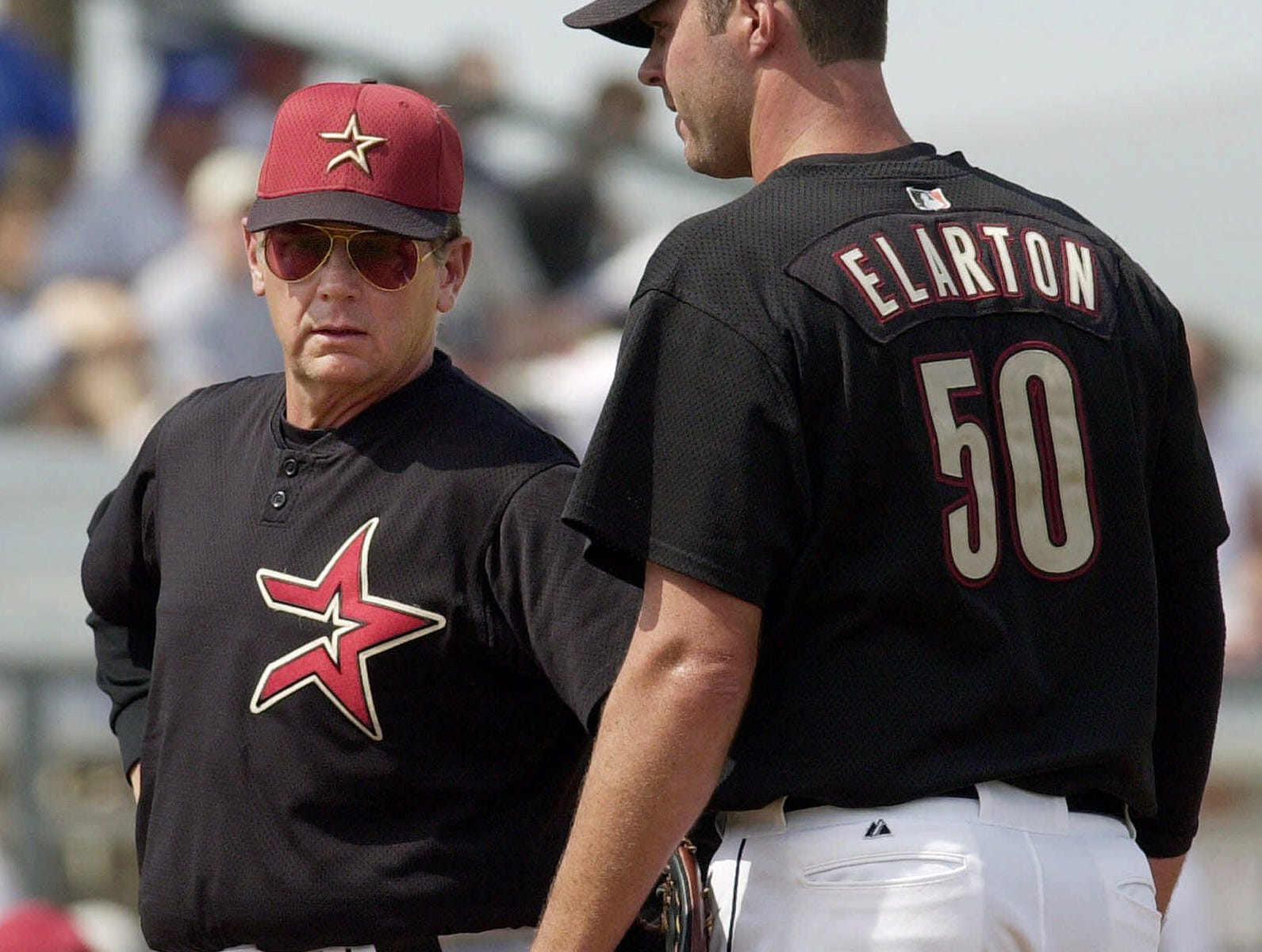 Houston Astros pitching coach Burt Hooton, left, talks to pitcher Scott Elarton during the third inning against the Pittsburgh Pirates, Friday, March 9, 2001, in Kissimmee, Fla. Elarton gave up six runs during the inning. The Pirates won 7-1. (AP Photo/Scott Audette)