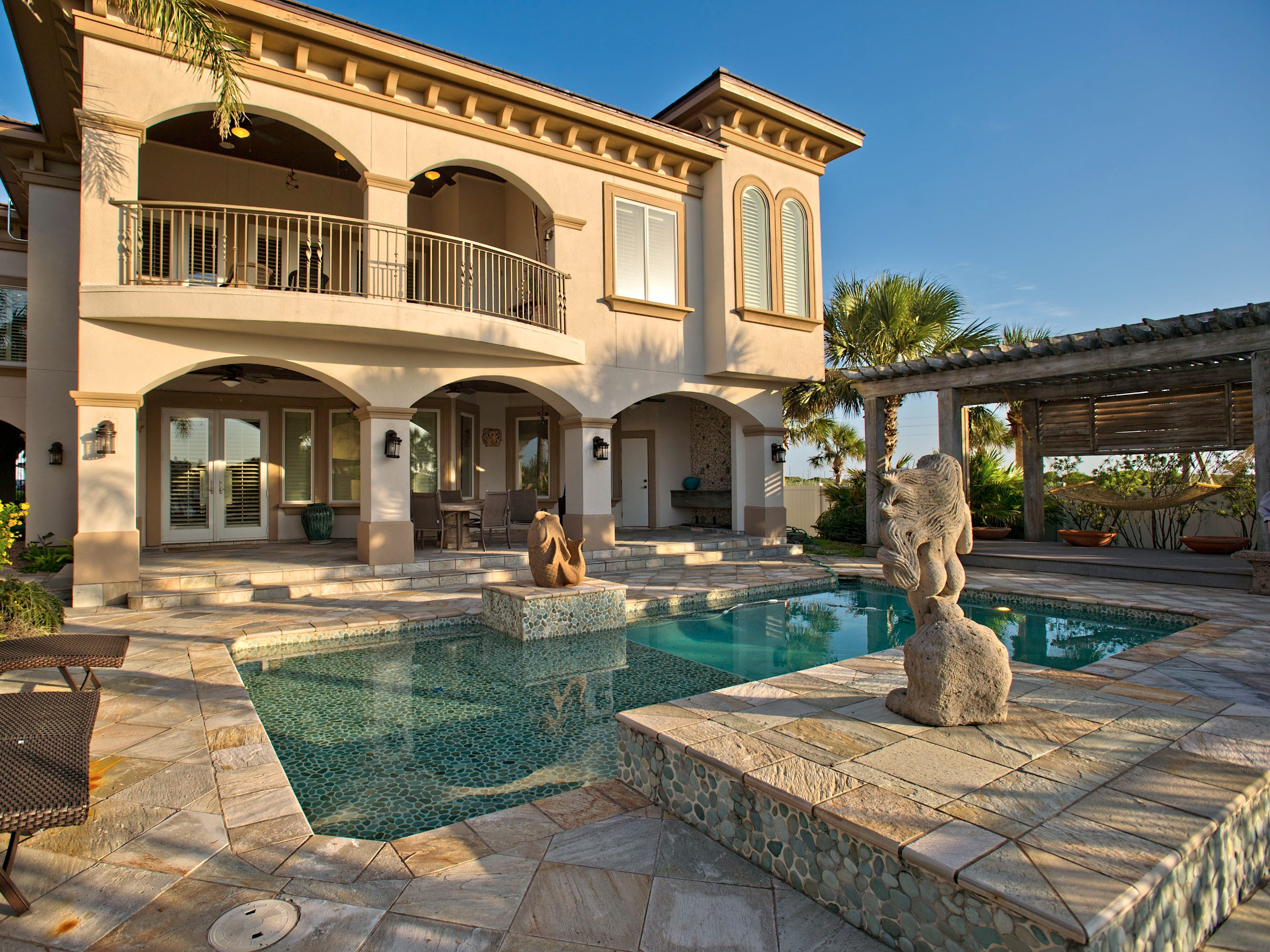 This Cabo-style resort home sits on the edge of a private marina with sunset, marina and ship channel views. Two boat slips with lifts,  a beautiful  slate tile covered pool area and private marina access in Port Aransas' incomparable gated La Joya subdivision.