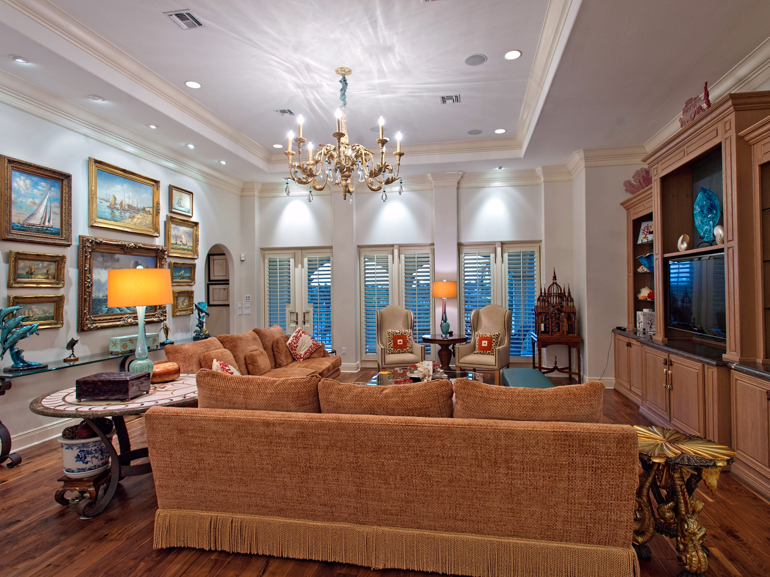 Coastal elegance abounds in the second floor living space with a beautiful crown molding, a wall of built ins and a wall of space  to display art; with a Brazilian wood floors