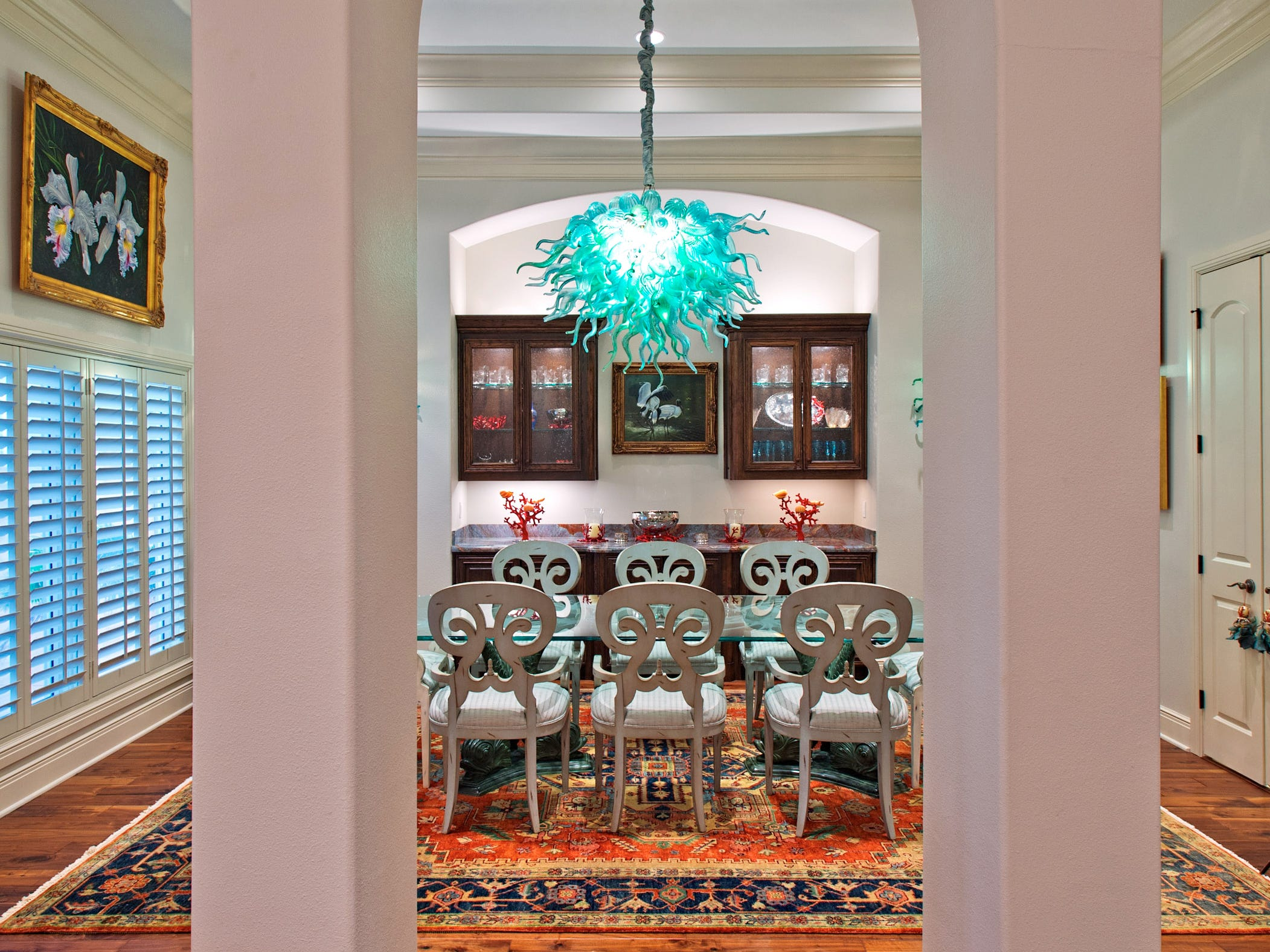 Chihuly inspired chandelier and sconces illuminate the dining room set behind a trio of archways, this room is quite simply stunning
