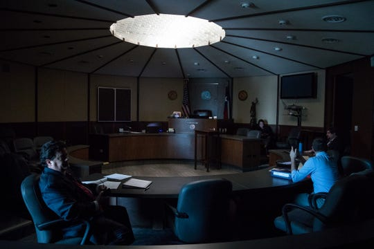 People sit in the 94th Texas courtroom after the power went out in the Nueces county courthouse on Wednesday, Aug. 1, 2018.