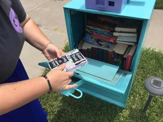 Liz Perez looks at the guest book that she put inside the Little Free Library.