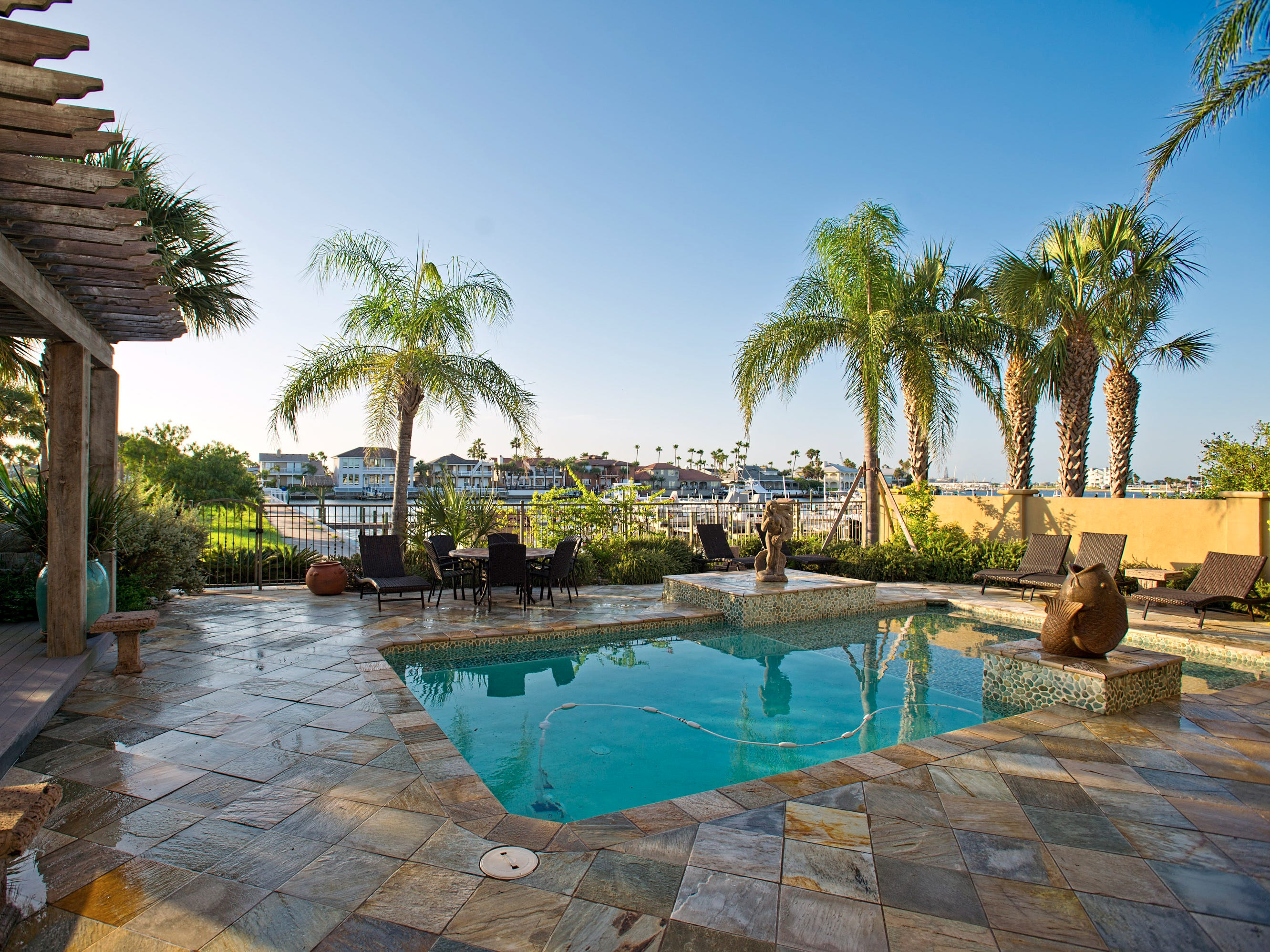 The a Baja entry pool accented with artisan stone is surrounded by  beautiful slate tile overlooking the Island Moorings Marina and the home's private boat slip, minutes away from world class fishing and the Gulf of Mexico at Port Aransas.