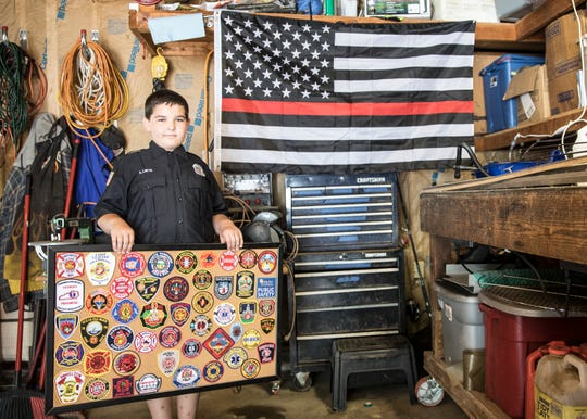 """Inside the garage that is referred to as """"Joe's Cave,"""" Adam Liste holds a board full of patches given to him by firefighters around the world while standing in front of the American Flag with a thin red line that honors firefighters injured and killed in the line of duty. Even with current events, Adam is determined to be a firefighter when he grows up and follow in Joe's footsteps."""