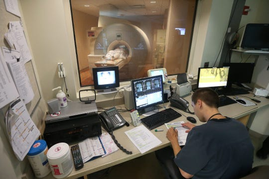 Bob Rulli, background, undergoes an MRI scan, administered by technologist Lance Miller, Tuesday, July 3, 2018, at Good Samaritan Hospital in Clifton.
