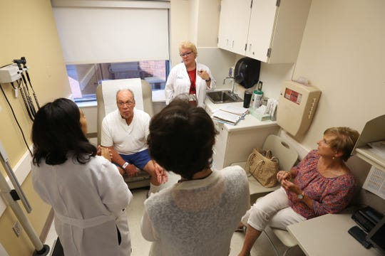 Bob, center, and Elise Rulli, far right, meet with a team of doctors in preparation for Bob's transfusion of the experimental drug BXQ-350, Tuesday, July 10, 2018, at the University of Cincinnati's Barrett Cancer Center in Cincinnati. Rulli of Fort Thomas is Patient No. 1 in a trial for a cancer drug discovered, developed and tested in Greater Cincinnati.