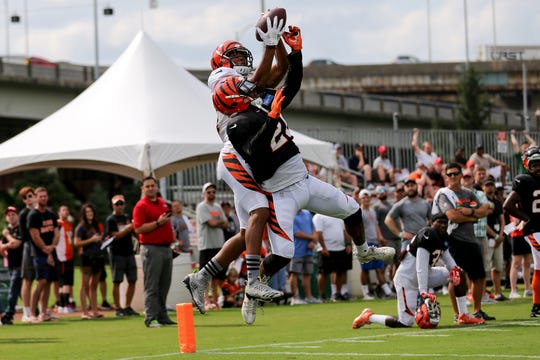 Cincinnati Bengals wide receiver Tyler Boyd (83) reaches over Cincinnati Bengals defensive back Darqueze Dennard (21) to complete a catch in the end zone during Cincinnati Bengals training camp practice, Wednesday, Aug. 1, 2018, on the practice fields next to Paul Brown Stadium in Cincinnati.