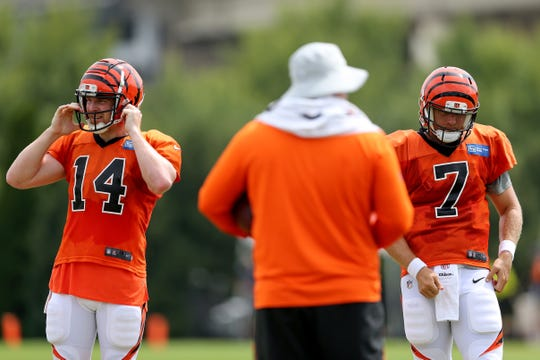Cincinnati Bengals quarterback Andy Dalton (14) and Cincinnati Bengals quarterback Matt Barkley (7) get set for a drill during Cincinnati Bengals training camp practice, Wednesday, Aug. 1, 2018, on the practice fields next to Paul Brown Stadium in Cincinnati.