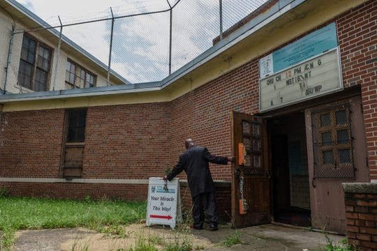 Elder Nathaniel Benson brings a sign inside the vacant school where church services are held for Total Life Change Ministries on Detroit's west side on Saturday, June 23, 2018.