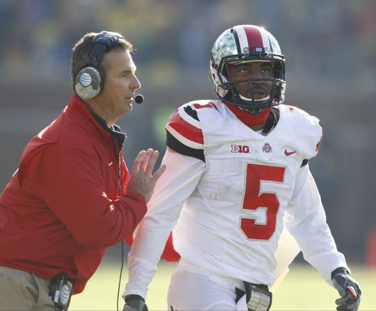 Ohio State head coach Urban Meyer gives quarterback Braxton Miller the play just before they scored late in the first half of their football game against Michigan in Ann Arbor on Saturday, November 30,  2013.