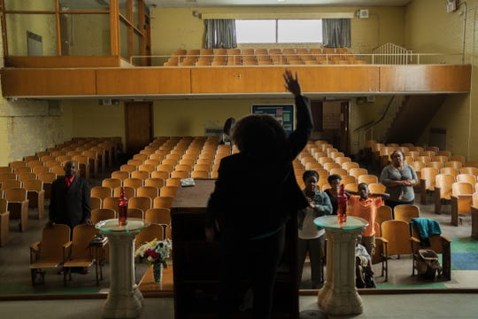 Apostle Shona Crossley-Beasley leads the congregation during services on June 23, 2018 in the auditorium of the defunct elementary school building where Total Life Change Ministries operates on Detroit's west side.