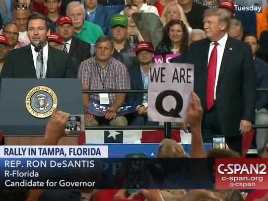 Rep. Ron Desantis speaks at a Trump rally in Tampa, Fla. on July 31, 2018. A QAnon sign is visible in the foreground.