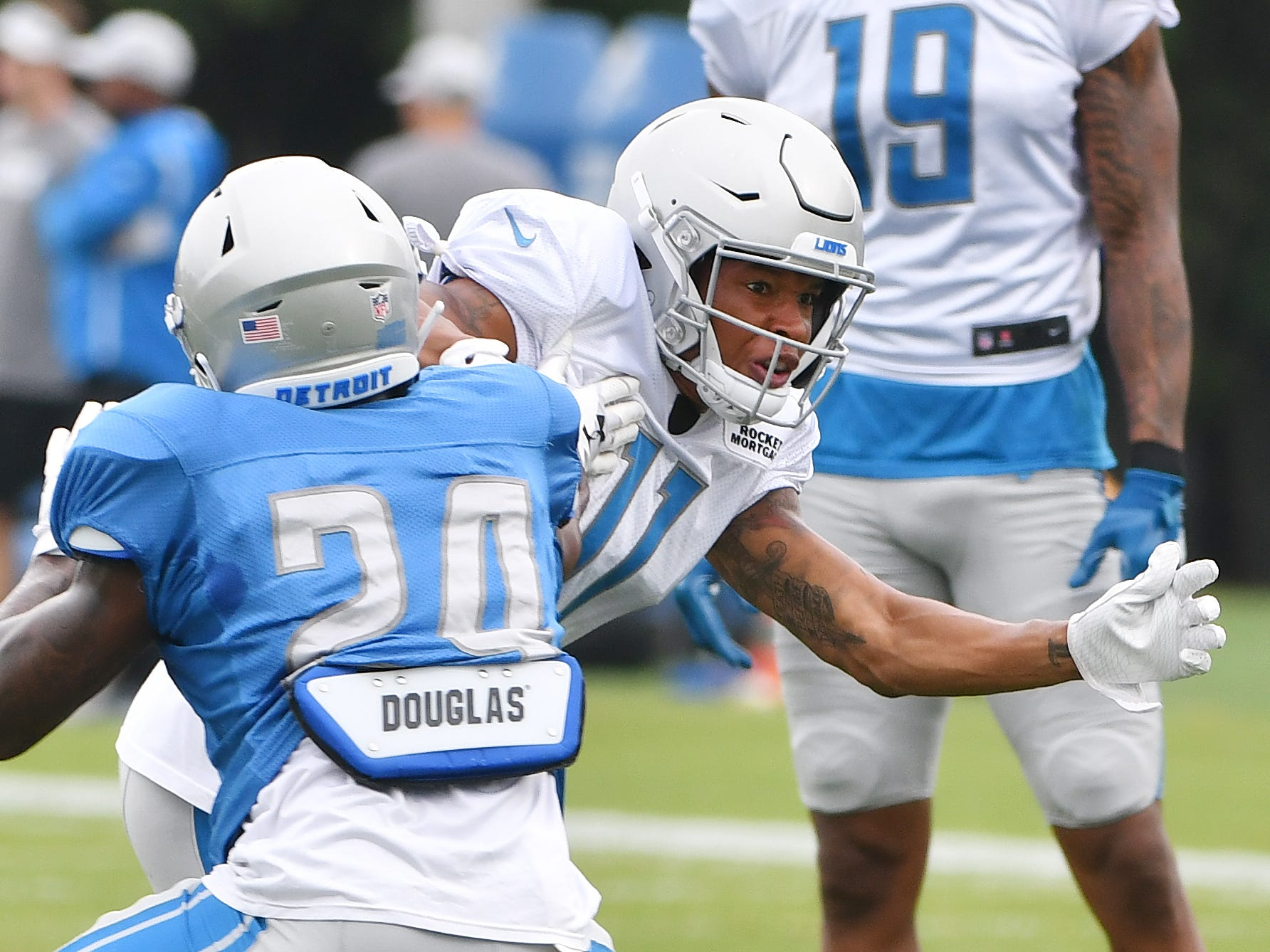 Lions cornerback Kevin Lawson and wide receiver Marvin Jones Jr. work during a drill involving bursting off the line of scrimmage against a defender.