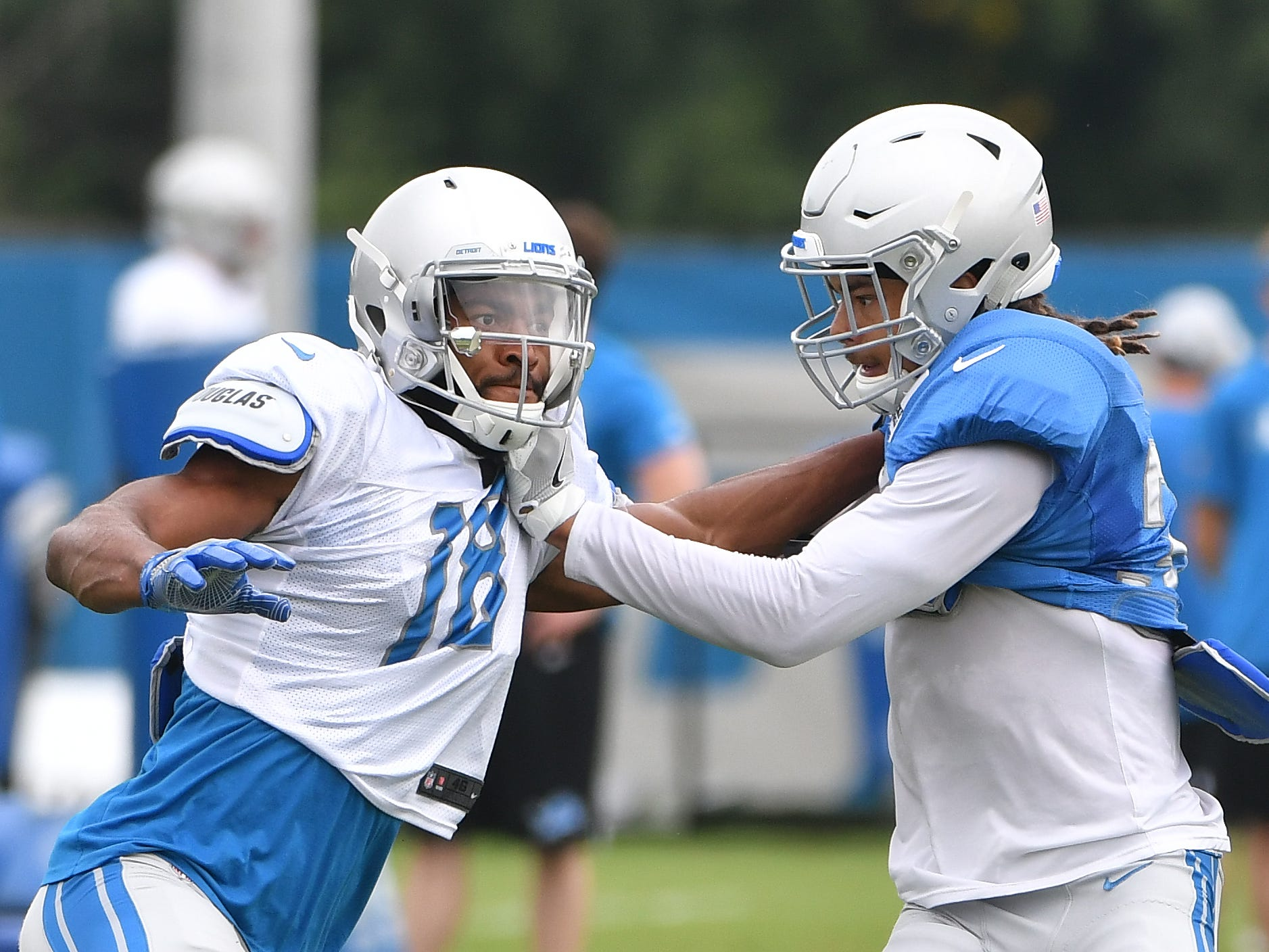 Lions wide receiver Chris Lacy and cornerback Mike Ford work during a drill involving bursting off the line of scrimmage against a defender.