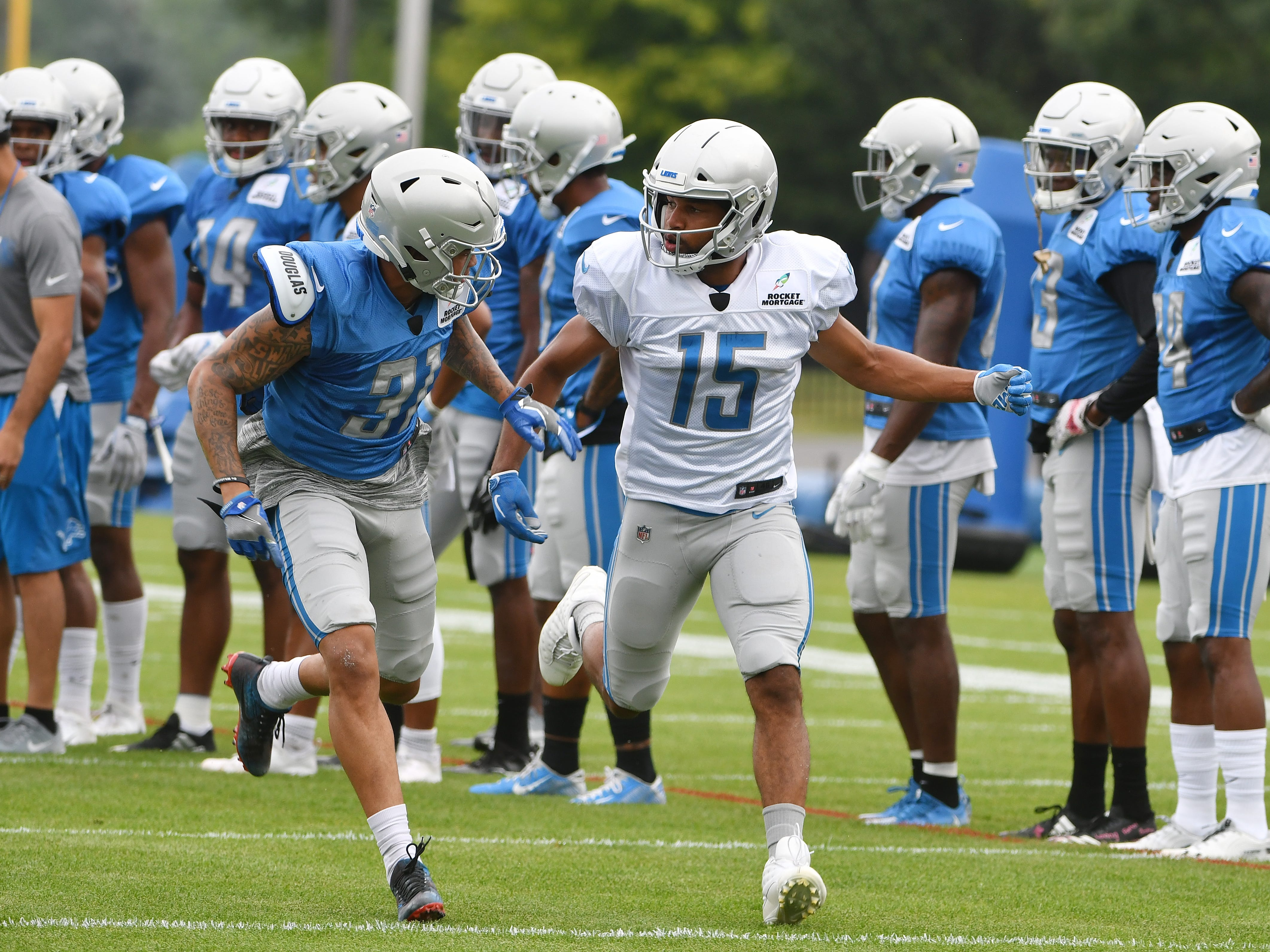 Lions cornerback Teez Tabor and wide receiver Golden Tate work during a drill involving bursting off the line of scrimmage against a defender.
