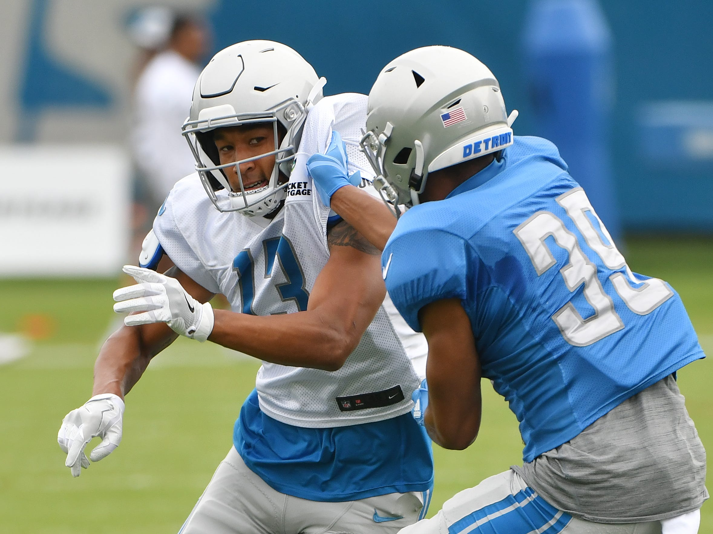 Lions wide receiver T.J. Jones and corner back Jamal Agnew work during a drill involving bursting off the line of scrimmage against a defender.