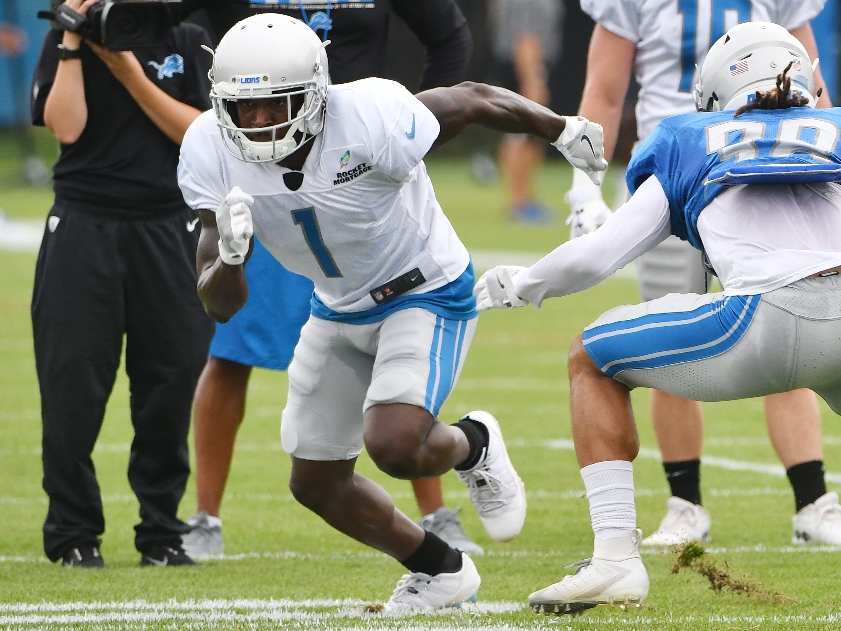 Lions wide receiver Brandon Powell and cornerback Mike Ford work during a drill involving bursting off the line of scrimmage against a defender.